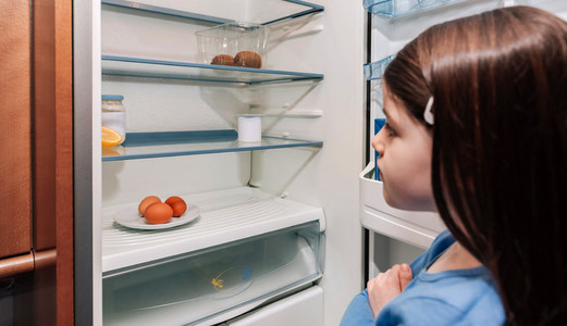 Girl looking at empty fridge due to a crisis