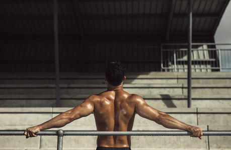 Muscular man resting in stadium stands