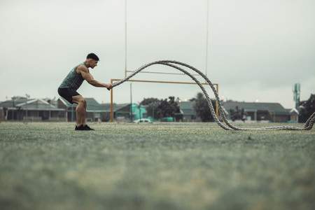 Athlete working out with battle ropes outdoors