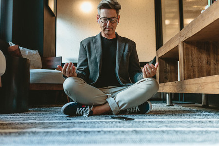 Businessman doing relaxation yoga in office lounge