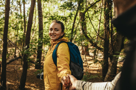 Happy couple on a camping trip walking in forest