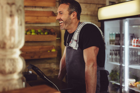 Smiling cafe worker standing at checkout counter