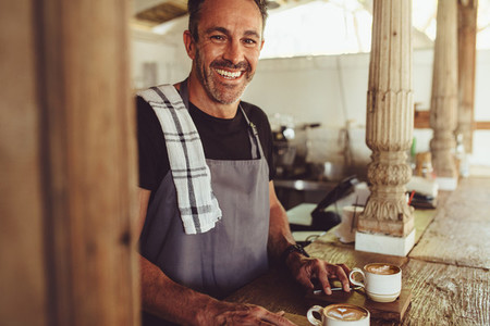 Happy male barista in a coffee shop