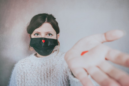 Young woman wearing a mask with a red heart on it
