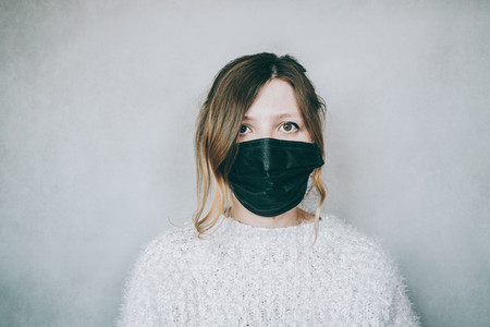 Young woman wearing a black face mask