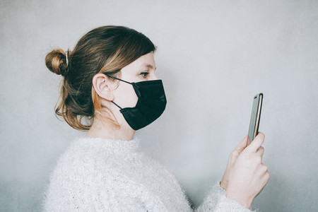 Young woman wearing a mask while use her smartphone