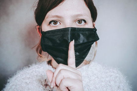 Young woman wearing a face mask and asking for silence