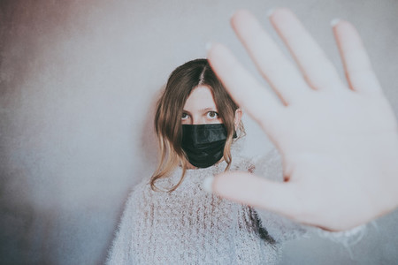 Young woman wearing a mask and put her hand for social distance