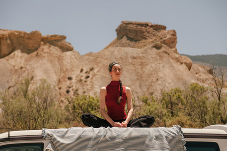Woman practicing yoga on the roof of a van in the desert