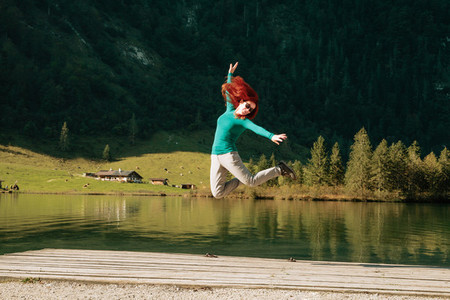 Young woman jumping on a pier near a lake under the mountains