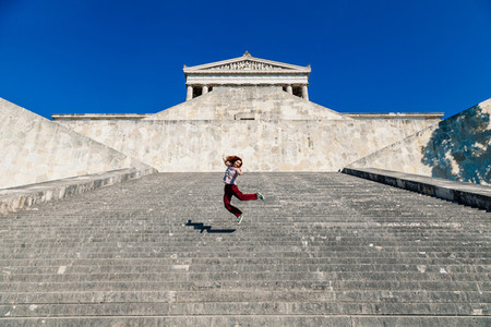 Young woman jumping on the walhalla stone stairs in germany