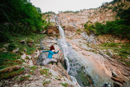Young woman jumping in a mountain near a waterfall