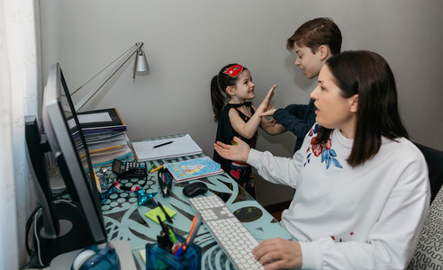 Woman working from home with her children bothering her