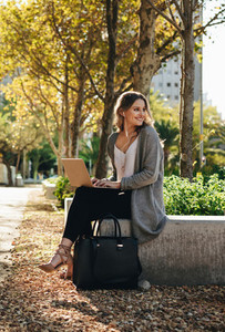 Smiling woman sitting outdoors with laptop