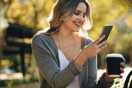 Businesswoman sitting outdoors using phone