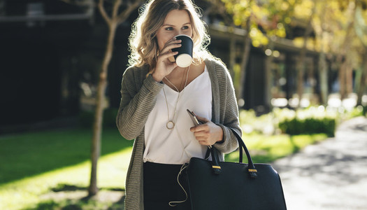 Businesswoman having coffee while commuting in the city
