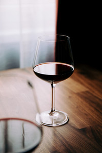 Red wine glass on a wooden table at home