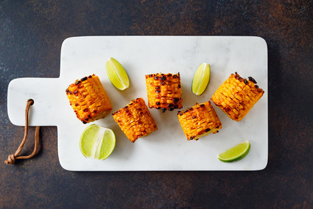 Roasted or grilled corn cob with olive oil and salt on a white marble tray Tasty simple recipe top view