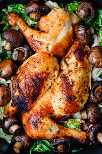 Top view of roasted chicken legs and breasts with fresh salad and mushrooms