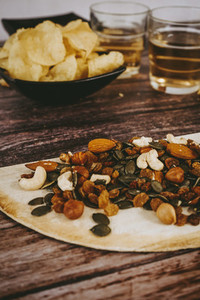 Mix of snacks with chips  nuts  seeds and beer