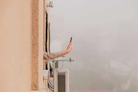 Woman arms out of the window using her phone during quarantine