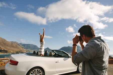 Man photographing woman in convertible car