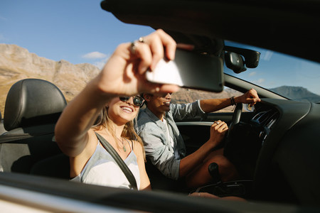 Couple on road trip in convertible car taking selfie
