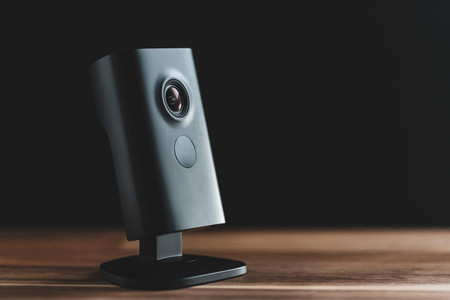Black minimalist CCTV camera at home on a wooden table