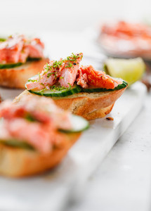 Toasts with fresh cucumber and smoked salmon served with lime shavings