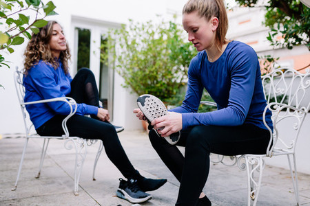 Two young sportswomen tying her shoelaces before the training