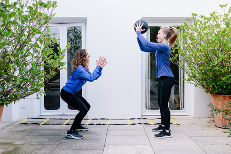 Two young women doing exercise together with medicine ball