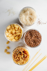 Various pasta and cereal grains in a plastic jars for a long storage