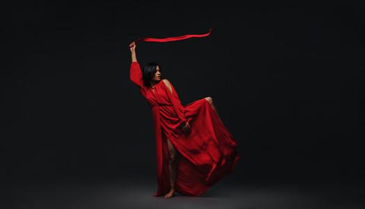 Dancer in red dress dancing in the dark studio