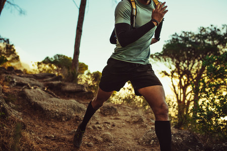 Mountain trail runner practicing on dirt path