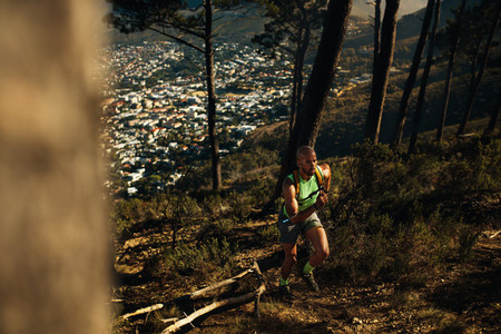 Fit sportsman sprinting over rocky trail