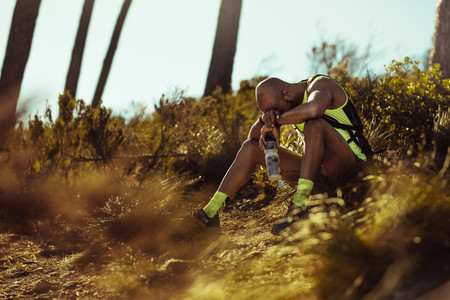 Trail runner taking break on mountain path