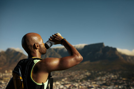 Athlete drinking water after morning run on mountain