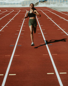 Woman runner training hard on a running track
