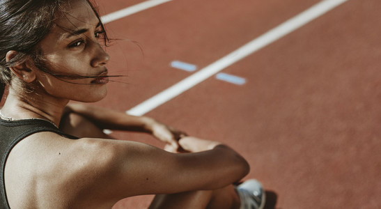 Fit woman after run sitting on race track