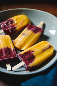Fruit homemade popsicles made are from fresh mango  blackcurrant and coconut milk  Healthy vegan summer dessert