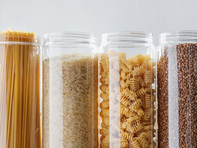 Various pasta and cereal grains in plastic jars for a long storage