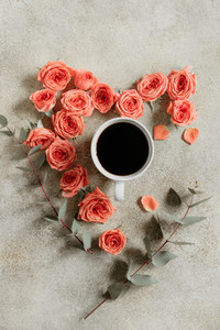 Cup of black coffee surrounded with fresh coral roses and eucalyptus branches on a textured beige background