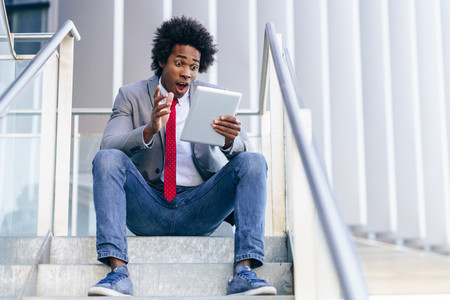 Black Businessman using a digital tablet sitting near an office building