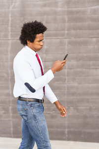 Concerned Black Businessman using his smartphone outdoors