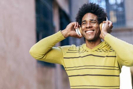 Black man listening to music with wireless headphones sightseeing in Granada