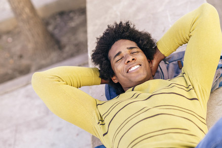 Black tourist with afro hair lying on the ground outdoors