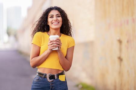 Arab girl walking across the street with a take away coffee