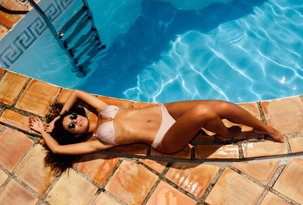 Beautiful woman with sunglasses lies on the edge of the swimming pool