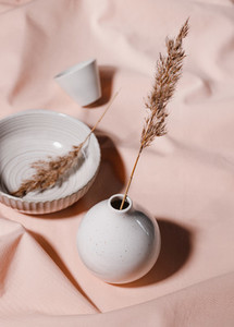 Abstract minimalist still life composition with ceramics and reeds over pink cloth