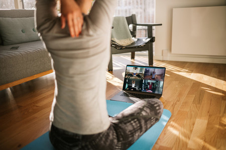 Fitness coach teaching yoga online to group of people